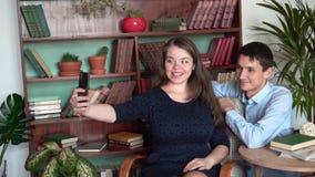 Grabben och flickan sitter i det hem- arkivet En flicka och en grabb poserar, gör en selfie arkivfilmer