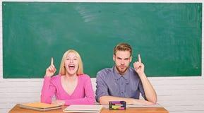 Grabben och flickan sitter p? skrivbordet i klassrum Korrekt svar p? deras mening Studera i h?gskola eller universitet Applicera  arkivbilder