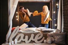 Grabben och flickan slåss med kuddar på sängen arkivbilder