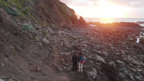 Grabben och flickaställningen på havet på solnedgången, på foten av klipporna, Benijo strand, Tenerife, kanariefågelöar arkivfilmer