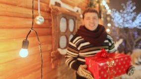 Grabben på bakgrunden av ett träfelikt hus ger en gåva till tittaren Tema för jul och för nytt år lager videofilmer