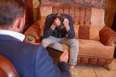 Grabben på soffan sitter på ett mottagande med en psykolog royaltyfri fotografi