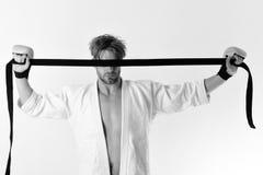 Grabben poserar i den vita kimonot som bär guld- boxninghandskar Mannen med gömd sikt rymmer det svarta bältet på vit bakgrund Arkivfoton