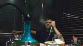 Grabben röker en vattenpipa och dricker öl i en nattklubb arkivfilmer