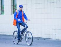 Grabben rider en cykel på trottoaren arkivbild