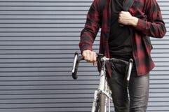 Grabben rymmer en cykel i hans hand och står mot en randig vägg, har studenten med en ryggsäck samlat och är klar arkivfoton