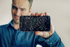 Grabben rymmer en svart smartphone med en bruten skärm Royaltyfria Bilder
