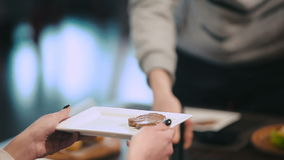 Grabben sätter på plattan grillade kött och grönsaker arkivfilmer