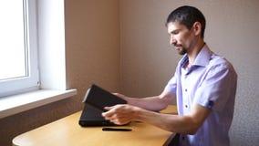 Grabben sätter telefonen på tabellen och tar anteckningsboken stock video