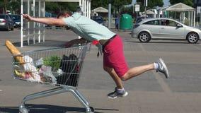 Grabben shoppar på supermarket galen shopping En spårvagn med mat lager videofilmer