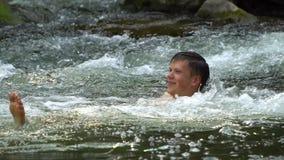 Grabben simmar i floden En ung gullig grabb badar i en ren bergflod Han är lycklig lager videofilmer