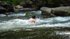 Grabben simmar i floden En ung gullig grabb badar i en ren bergflod Han är lycklig arkivfilmer