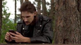 Grabben sitter med telefonen i träna stock video
