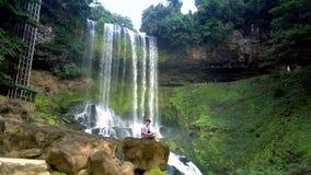 Grabben sitter vaggar på styrning surrar mot vattenfallet arkivfilmer