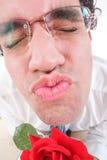 Grabben som försöker att vara romantiker som ger ett kyssinnehav, steg Fotografering för Bildbyråer