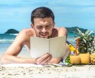 Grabben som ligger på stranden och läsningen en bok på bakgrunden Royaltyfri Fotografi