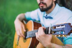Grabben som spelar gitarren på gräsmattan royaltyfria foton