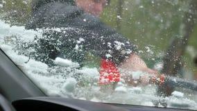 Grabben sopar snön från dettäckte bilfönstret arkivfilmer
