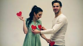 Grabben stänger bröstkorgen för flicka` s med två hjärtor på en vit bakgrund En grabb med en flicka är kyssande på dag för valent stock video