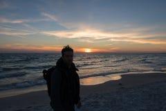 Grabben står framme av dramatisk solnedgång över havet royaltyfria foton