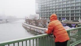 Grabben står på bron och blickarna på staden i dimman i Österrike arkivfilmer