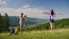 Grabben tar bilder av hans flickvän i ett pittoreskt ställe på bakgrunden av bergen Närliggande var deras arkivfilmer