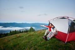 Grabben visar hans hand i avståndssammanträde på tältet nära flicka från mot Carpathian berg royaltyfri bild