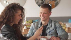 Grabben visar hans kvinnliga vän något på hans smartphone på kafét stock video