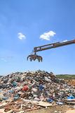 Grabber crane over garbage Royalty Free Stock Photography