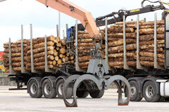 Grabber crane with timber. Grabber crane for loading and unloading timber and wood from road transport Stock Image