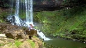 Grabbflickan sitter vaggar på vid vattenfallet parkerar in arkivfilmer