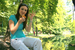 Grabbing a bite. A young woman sitting on a log in the park, grabbing a bite as she rests Royalty Free Stock Photos