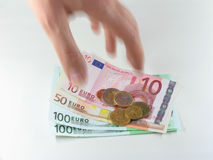 Grabbing Euros. A hand grabbing some Euro coins and bills Stock Photo