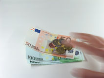 Grabbing money. A hand grabbing Euro bills and coins very fast Royalty Free Stock Images