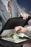 Grabbing money. Female hand grabbing cash dollars from a file hold my formally dressed male Royalty Free Stock Photo