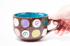 Grabbing Painted Mug. A macro selective shot of a hand grabbing a painted mug in a studio. focus on front of Mug Stock Image