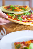Grabbing a slice of Pizza. Female hand grabs for a slice of italian style pizza with arugula and prosciutto Stock Image