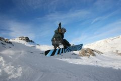 Grabbing Snowboarder. Snowboarder jumping and grabbing board between legs Stock Images