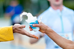 Grabbing water during a marathon. Runner grabbing water during a marathon from a volunteer hand. Use of selective focus Stock Image