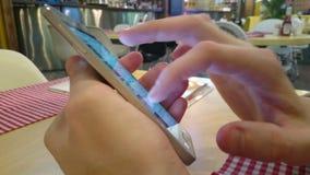 Grabbsammanträde på restaurangen som bläddrar samkvämmen, knyter kontakt på smartphonen arkivfilmer