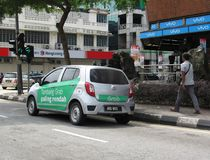 GrabCar Taxi With Promotional Ads Painted Around Its Side. The ride-hailing/ride-sharing service GrabCar in the streets of Ipoh city, Malaysia Stock Photos