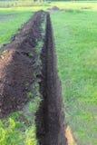 Graben im Boden am Rasen Stockfotos