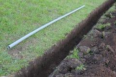 Graben im Boden und im grauen Kunststoffrohr Stockfotos