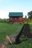 Graben im Boden und im kleinen Haus Stockbilder