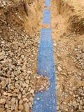 Graben mit blauem Plastikschutzband Markiert von den Kabeln unter Lehm während des Gebäudes des Internets Stockfoto