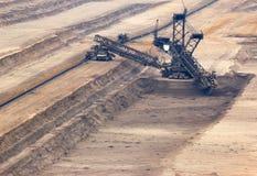 Grabende Braunkohle des Baggers in der Tagebaugrube Lizenzfreie Stockfotos