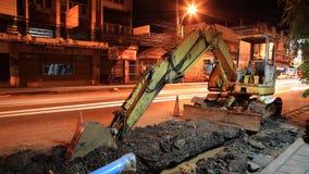 Grabende Straße des gelben Exkavators nachts Lizenzfreies Stockbild