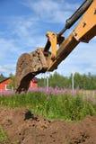 Grabender Boden des Baggers gegen Häuser und Weidekrauthintergrund Lizenzfreies Stockfoto