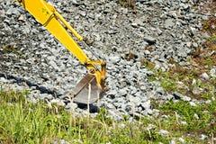 Grabender Felsen der Baggerschaufel Lizenzfreies Stockfoto