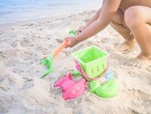 Grabender Sand des asiatischen Jungen mit buntem Spielzeug Stockfotos